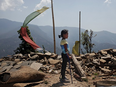 Khendo Tamang, 8, stands near the debris of the collapsed home she was trapped in after the earthquake struck in Banskharka. AP