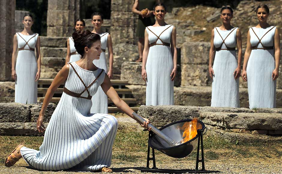 Greek actress Katerina Lehou , playing the role of High Priestess, lights a torch from the sun's rays reflected in a parabolic mirror during the dress rehearsal for the Olympic flame lighting ceremony for the Rio 2016 Olympic Games at the site of ancient Olympia in Greece, April 20, 2016. REUTERS/Yannis Behrakis