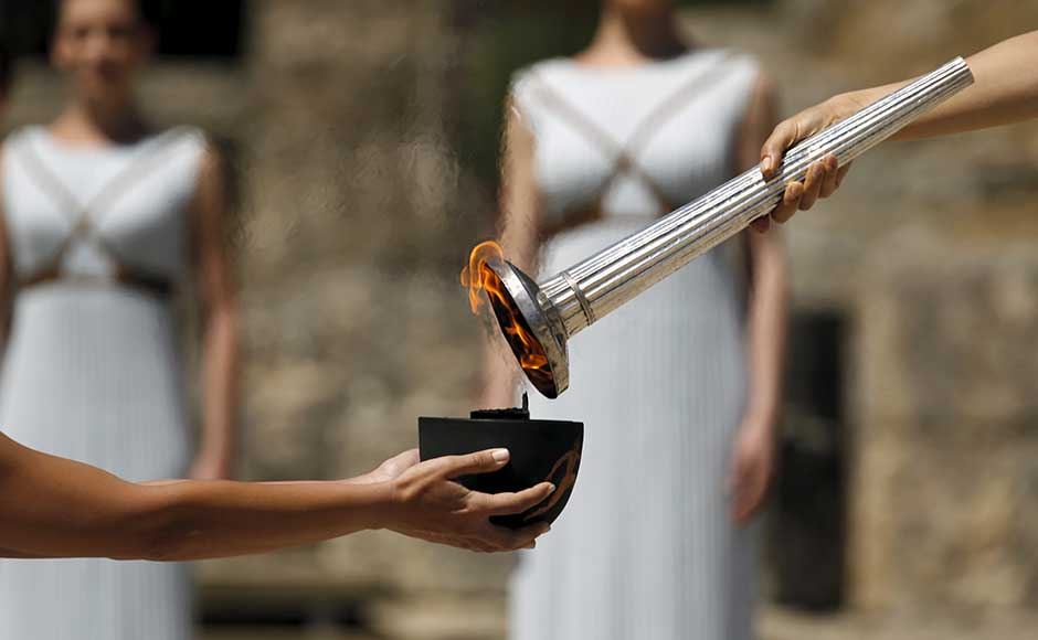 Greek actress Katerina Lehou, playing the role of High Priestess, passes the Olympic flame to a priestess during the dress rehearsal for the Olympic flame lighting ceremony for the Rio 2016 Olympic Games at the site of ancient Olympia in Greece, April 20, 2016. REUTERS/Yannis Behrakis