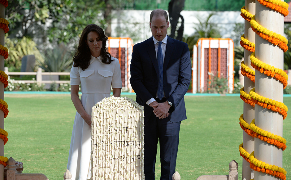 Britain's Prince William, Duke of Cambridge(R)and his wife Catherine, Duchess of Cambridge bow their heads as they pay tribute during a visit to Gandhi Smiriti, an Indian museum dedicated to Mahatma Gandhi in New Delhi on April 11, 2016. / AFP PHOTO