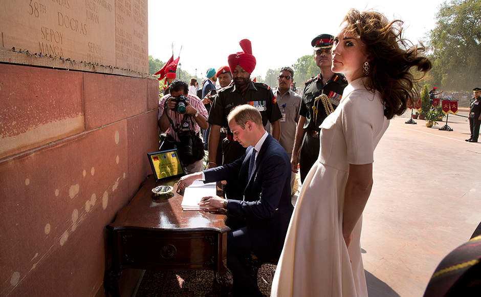 Britain's Prince William,Duke of Cambridge(C)signs the visitor's book as his wife Catherine Duchess of Cambridge(R)looks on after paying tribute at the India Gate war memorial, in the memory of the soldiers from Indian regiments who served in World War I, in New Delhi on April 11, 2016. / AFP PHOTO