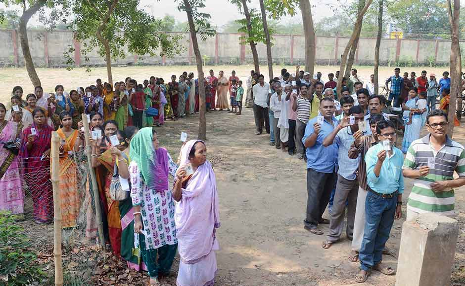 Voters wait in queues to cast votes at a polling station during the state assembly elections in Kharagpur, West Bengal on Monday. PTI