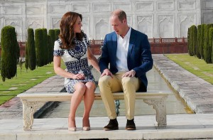 Britain's Prince William, along with his wife, Kate, the Duchess of Cambridge, talk to each other as they pose in front of the Taj Mahal in Agra on Saturday. PTI