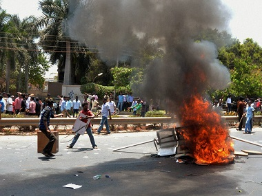 Garment workers torch furniture during a protest over EPF withdrawal norm, in Bengaluru on Tuesday. PTI