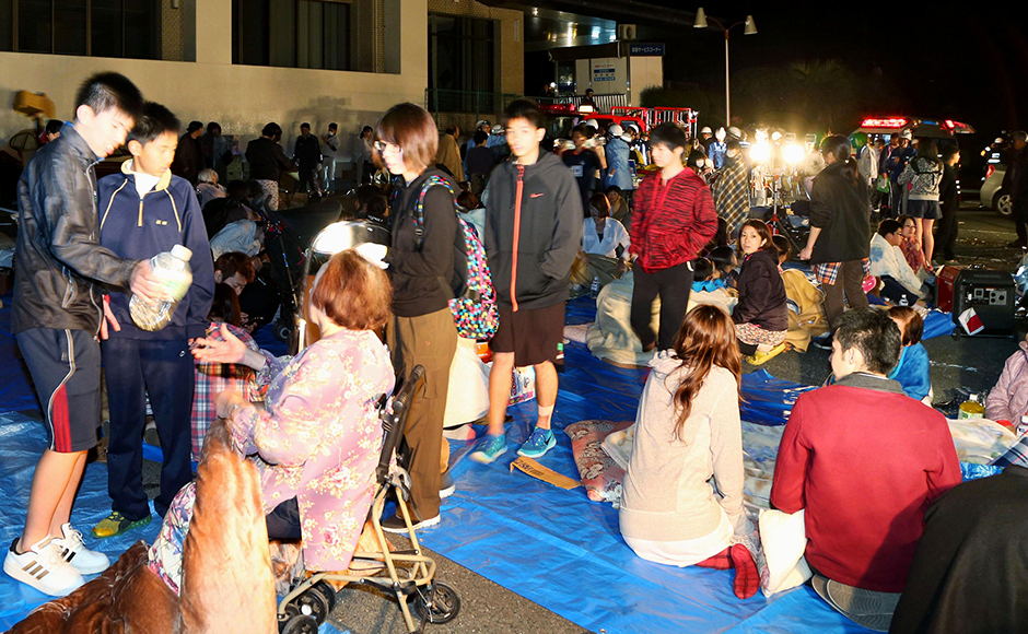 Stranded people gather outside a town hall of Mashiki, after an earthquake in Kumamoto, southern Japan, Thursday, April 14, 2016. A powerful earthquake with a preliminary magnitude of 6.4 has struck southern Japan, collapsing walls and a number of houses. AP