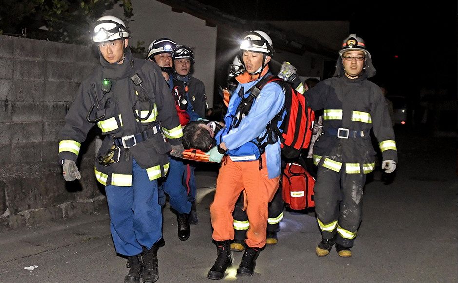 Firefighters carry an injured after the earthquake, at the town of Mashiki, in Kumamoto, southern Japan, Thursday, April 14, 2016. A powerful earthquake with a magnitude of 6.5 knocked over buildings in southern Japan on Thursday evening, and police said people may be trapped underneath. AP
