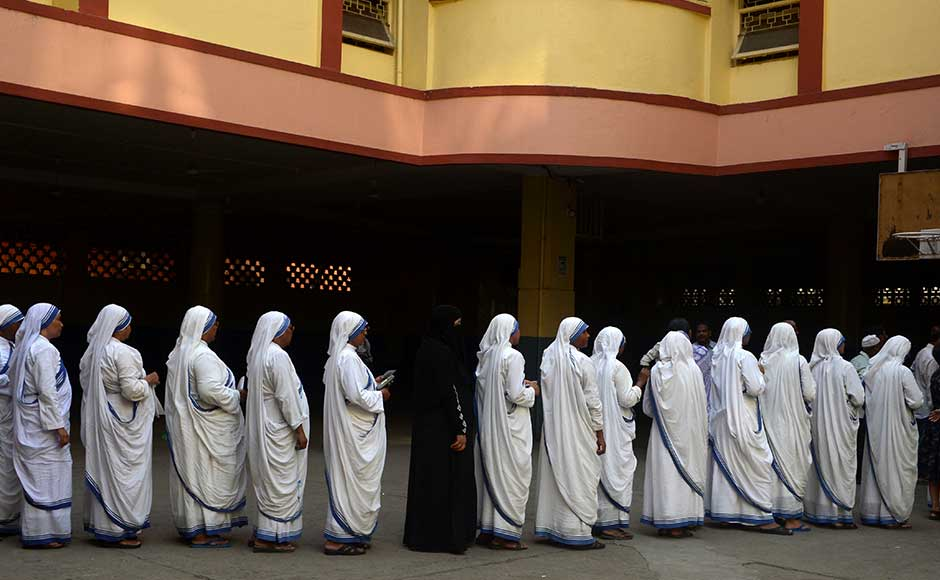 Indian Christian nuns from the Catholic Order of the Missionaries of Charity queue as they wait to cast their votes for state assembly elections inside a polling station in Kolkata on April 21, 2016. State assembly elections in West Bengal are taking place in five phases from April 4 to May 5. AFP