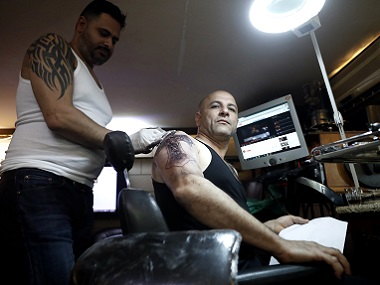 Christian Palestinian tattoo artist Walid Ayash (L) draws a tattoo depicting a crucified Jesus Christ on the arm of a Coptic Egyptian pilgrim, at his studio in the West Bank town of Bethlehem. AFP