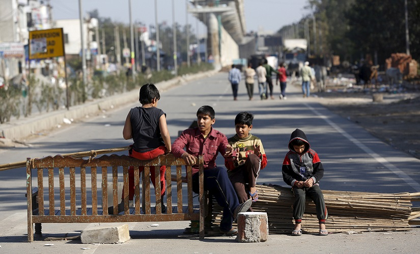 Children sit on a road blockade by the demonstrators from the Jat community to block the Delhi-Haryana national highway during a protest at Sankhol