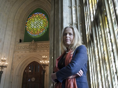 "Artist Mary Branson poses in front of her art work ""New Dawn"". UK Parliament via AP"
