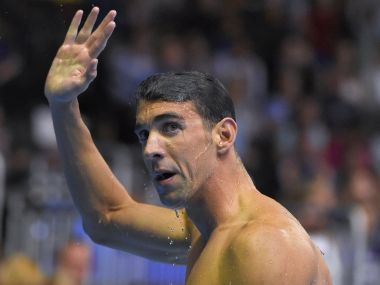 Michael Phelps waves to fans after swimming in a men's 200-meter butterfly semifinal at the US Olympic swimming trials. AP