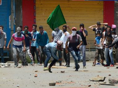Protesters throw stones at police during a clash that broke out in Bemina, Srinagar on Tuesday. PTI
