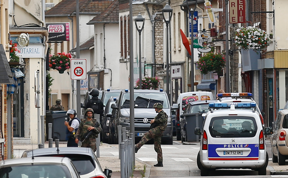 French soldiers stand guard near the scene of an attack in Saint-Etienne-du-Rouvray, Normandy, France, Tuesday, July 26, 2016. Two attackers invaded a church Tuesday during morning Mass near the Normandy city of Rouen, killing an 84-year-old priest by slitting his throat and taking hostages before being shot and killed by police, French officials said. (AP Photo/Francois Mori)
