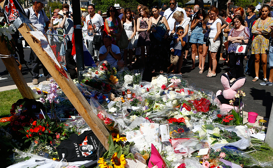 People gather by flowers laid near the scene where a truck mowed through revelers in Nice, southern France, Friday, July 15, 2016. A large truck mowed through revelers gathered for Bastille Day fireworks in Nice, killing more than 80 people and sending people fleeing into the sea as it bore down for more than a mile along the Riviera city's famed waterfront promenade. (AP Photo/Francois Mori)