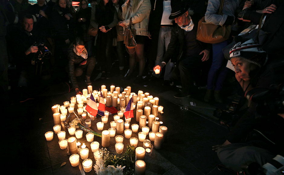 People place candles in a circle during a vigil in a tribute to the victims of the Bastille Day tragedy, in Sydney, Australia, Friday, July 15, 2016. World leaders are expressing dismay, sadness and solidarity with France over the attack carried out by a man who drove truck into crowds of people celebrating France's national day in Nice. (AP Photo/Rob Griffith)