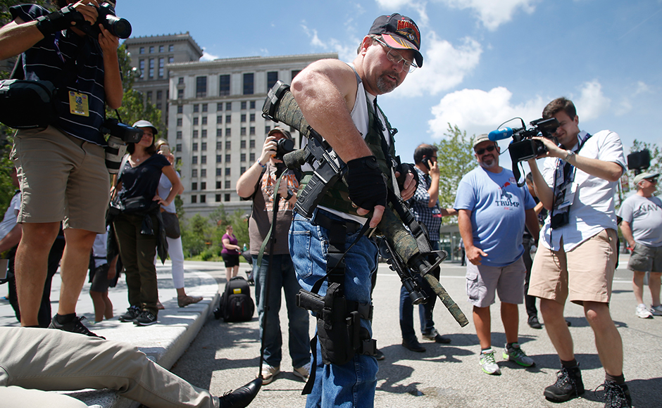 Steve Thacker carrying a rifle and a handgun is surrounded by news media in a public square in Cleveland, Ohio, U.S., July 17, 2016. (REUTERS/Jim Urquhart)