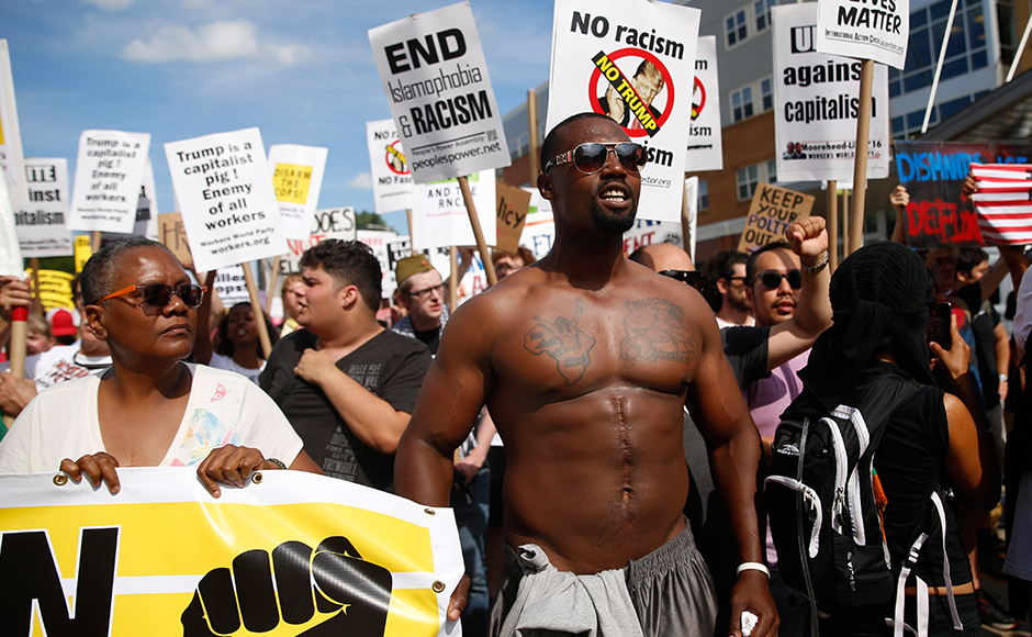 "Demonstrators hold placards during a march by various groups, including ""Black Lives Matter"" and ""Shut Down Trump and the RNC"" ahead of the Republican National Convention in Cleveland, Ohio, U.S. July 17, 2016. (REUTERS/Shannon Stapleton)"