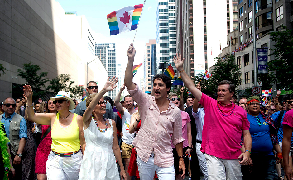 Ontario Premier Kathleen Wynne, left to right, Prime Minister Justin Trudeau and Toronto Mayor John Tory wave to spectators at the annual Pride Parade in Toronto on Sunday, July 3, 2016. (Nathan Denette/The Canadian Press via AP)