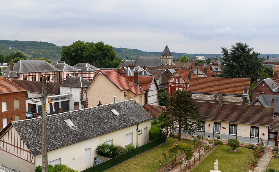 General view of the town of Saint-Etienne-du-Rouvray, Normandy, France, where a 84-year-old priest was murdered in a church, in background, during an attack, Tuesday, July 26, 2016. Two attackers invaded a church Tuesday during morning Mass near the Normandy city of Rouen, killing an 84-year-old priest by slitting his throat and taking hostages before being shot and killed by police, French officials said. (AP Photo/Francois Mori)