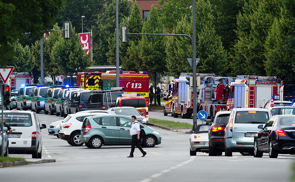 Police cars and fire trucks stand near a shopping centre in which a shooting was reported in Munich, southern Germany, Friday, July 22, 2016. Situation after a shooting in the Olympia shopping centre in Munich is unclear. (Matthias Balk/dpa via AP)