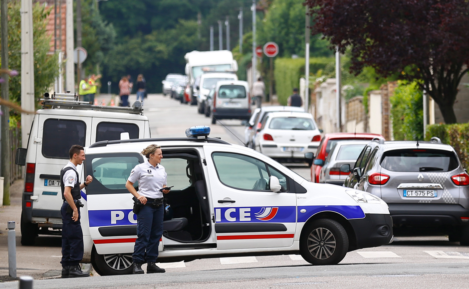 French police officers prevent the access to the scene of an attack in Saint Etienne du Rouvray, Normandy, France, Tuesday, July 26, 2016. Two attackers invaded a church Tuesday during morning Mass near the Normandy city of Rouen, killing an 84-year-old priest by slitting his throat and taking hostages before being shot and killed by police, French officials said. (AP Photo/Francois Mori)