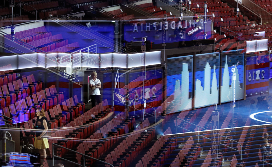 Seen through a reflection of the stage in a window, people stand in the seats during preparations before the 2016 Democratic Convention, Sunday, July 24, 2016, in Philadelphia. (AP Photo/John Locher)