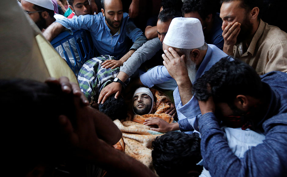 Family members and relatives mourn next to the body of Burhan Wani, a separatist militant leader, during his funeral in Tral, south of Srinagar, July 9, 2016. REUTERS