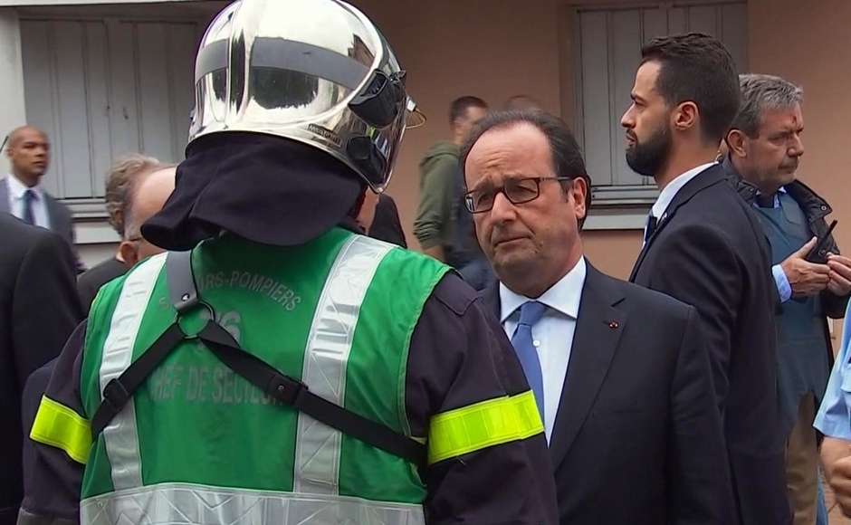 In this grab made from video, French President Francois Hollande speaks with emergency services personnel after arriving at the scene of the hostage situation in Normandy, France, Tuesday, July 26, 2016. Two attackers took hostages inside a French church during morning Mass on Tuesday in the Normandy town of Saint-Etienne-du-Rouvray, killing an 86-year-old priest by slitting his throat before being shot and killed by police, French officials said. The Islamic State group claimed responsibility for the attack. (France Pool via AP)