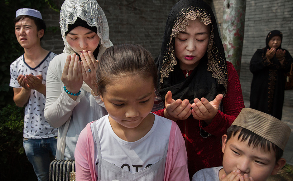 CHINA - JULY 06: A Chinese Hui Muslim family prays at the 'Sheiks Tombs' after Eid al-Fitr prayers marking the end of the holy fasting month of Ramadan at the historic Niujie Mosque on July 6, 2016 in Beijing, China. Islam in China dates back to the 10th century as the legacy of Arab traders who ventured from the Middle East along the ancient Silk Road. Of an estimated 23 million Muslims in China, roughly half are Hui, who are ethnically Chinese and speak Mandarin. China's constitution provides for Islam as one of five 'approved' religions in the officially atheist country though the government enforces severe limits. Worship is permitted only at state-sanctioned mosques and proselytizing in public is illegal. The Hui, one of 55 ethnic minorities in China (along with the Han majority), have long nurtured a coexistence with the Communist Party and is among the minority groups with political representation at various levels of government. The Hui Muslim population fast from dawn until dusk during Ramadan and it is believed there are more than 20 million members of the community in the country. (Photo by Kevin Frayer/Getty Images)