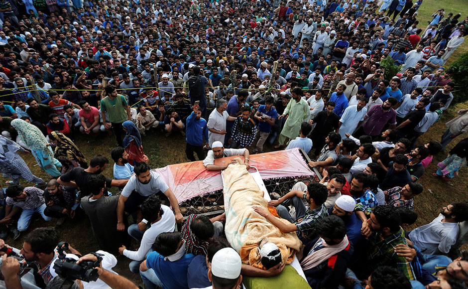 Kashmiri Muslims gather around the body of Burhan Wani, a separatist militant leader, during his funeral in Tral, south of Srinagar, July 9, 2016. REUTERS