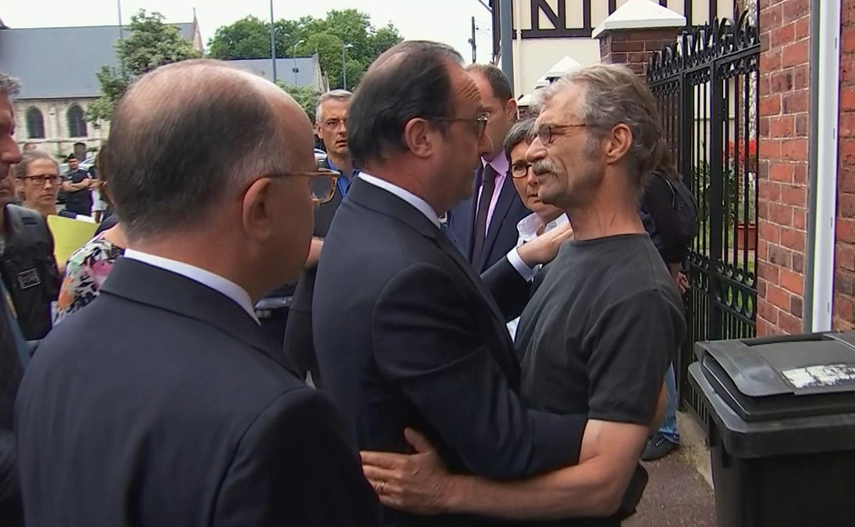 In this grab made from video, French President Francois Hollande, center, and Interior Minister Bernard Cazeneuve speaks with a local man after arriving at the scene of the hostage situation in Normandy, France, Tuesday, July 26, 2016. Two attackers took hostages inside a French church during morning Mass on Tuesday in the Normandy town of Saint-Etienne-du-Rouvray, killing an 86-year-old priest by slitting his throat before being shot and killed by police, French officials said. The Islamic State group claimed responsibility for the attack. (France Pool via AP)