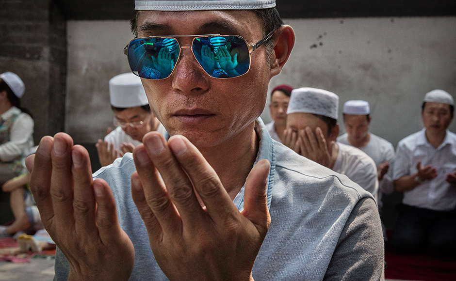 CHINA - JULY 06: Chinese Hui Muslim men pray during Eid al-Fitr prayers marking the end of the holy fasting month of Ramadan at the historic Niujie Mosque on July 6, 2016 in Beijing, China. Islam in China dates back to the 10th century as the legacy of Arab traders who ventured from the Middle East along the ancient Silk Road. Of an estimated 23 million Muslims in China, roughly half are Hui, who are ethnically Chinese and speak Mandarin. China's constitution provides for Islam as one of five 'approved' religions in the officially atheist country though the government enforces severe limits. Worship is permitted only at state-sanctioned mosques and proselytizing in public is illegal. The Hui, one of 55 ethnic minorities in China (along with the Han majority), have long nurtured a coexistence with the Communist Party and is among the minority groups with political representation at various levels of government. The Hui Muslim population fast from dawn until dusk during Ramadan and it is believed there are more than 20 million members of the community in the country. (Photo by Kevin Frayer/Getty Images)