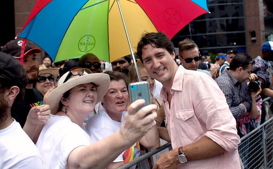 Prime Minister Justin Trudeau poses for a photo as he greets spectators at the annual Pride Parade in Toronto on Sunday, July 3, 2016. (Mark Blinch/The Canadian Press via AP)