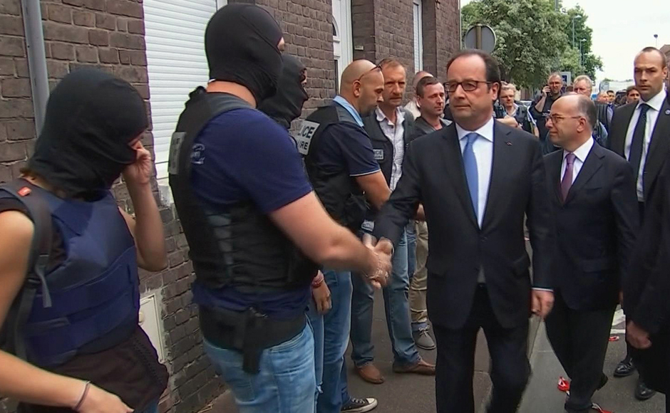 In this grab made from video, French President Francois Hollande shakes hands with police and security services personnel after arriving at the scene of the hostage situation in Saint-Etienne-du-Rouvray Normandy, France, Tuesday, July 26, 2016. Two attackers took hostages inside a French church during morning Mass on Tuesday near the city of Rouen, killing an 86-year-old priest by slitting his throat before being shot and killed by police, French officials said. The Islamic State group claimed responsibility for the attack. (France Pool via AP)