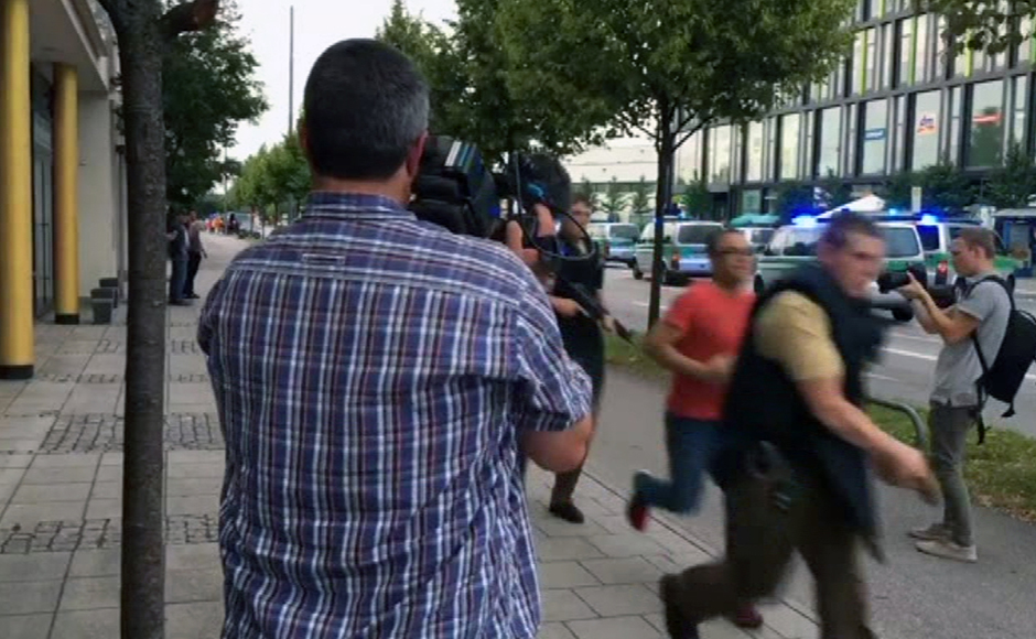 Armed police move past onlooking media responding to a shooting at a shopping center in Munich, Germany, Friday July 22, 2016. Munich police confirm shots have been fired at Olympia Einkaufszentrum shopping center but say they don't have any details about casualties. Police are responding in large numbers. (AP Photo/APTV)