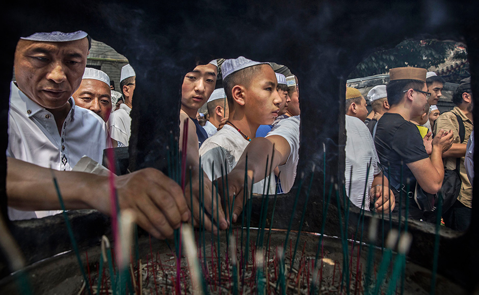 CHINA - JULY 06: Chinese Hui Muslim men light incense at the 'Sheiks Tombs' after Eid al-Fitr prayers marking the end of the holy fasting month of Ramadan at the historic Niujie Mosque on July 6, 2016 in Beijing, China. Islam in China dates back to the 10th century as the legacy of Arab traders who ventured from the Middle East along the ancient Silk Road. Of an estimated 23 million Muslims in China, roughly half are Hui, who are ethnically Chinese and speak Mandarin. China's constitution provides for Islam as one of five 'approved' religions in the officially atheist country though the government enforces severe limits. Worship is permitted only at state-sanctioned mosques and proselytizing in public is illegal. The Hui, one of 55 ethnic minorities in China (along with the Han majority), have long nurtured a coexistence with the Communist Party and is among the minority groups with political representation at various levels of government. The Hui Muslim population fast from dawn until dusk during Ramadan and it is believed there are more than 20 million members of the community in the country. (Photo by Kevin Frayer/Getty Images)