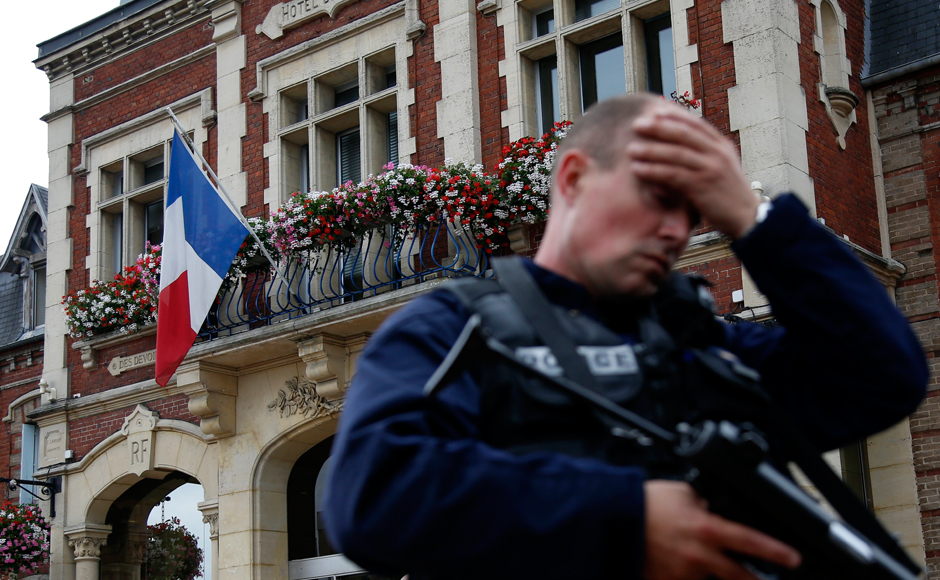 A policeman reacts as he secures a position in front of the city hall after two assailants had taken five people hostage in the church at Saint-Etienne-du -Rouvray near Rouen in Normandy, France, July 26, 2016. Two attackers killed a priest with a blade and seriously wounded another hostage in a church in northern France on Tuesday before being shot dead by French police. (REUTERS/Pascal Rossignol)