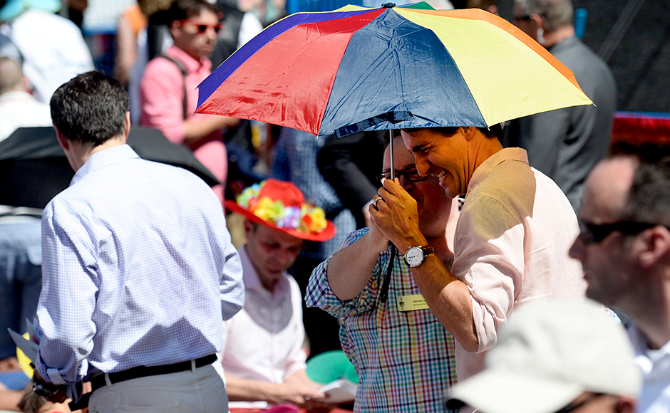Prime Minister Justin Trudeau holds a rainbow umbrella as he greets spectators at the annual Pride Parade in Toronto on Sunday, July 3, 2016. (Nathan Denette/The Canadian Press via AP)