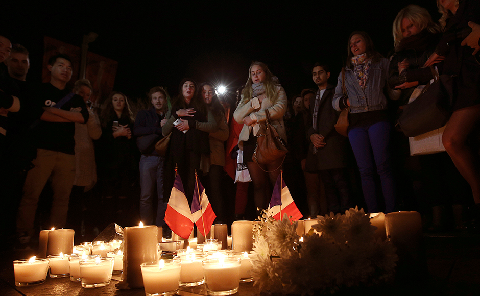 People stand around a circle of candles during a moment of silence at a vigil to honor victims of the Bastille Day tragedy in Nice, France, in Sydney, Australia, Friday, July 15, 2016. World leaders are expressing dismay, sadness and solidarity with France over the attack carried out by a man who drove truck into crowds of people celebrating France's national day in Nice. (AP Photo/Rob Griffith)