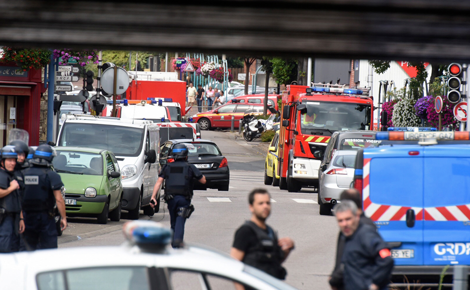 Police and rescue workers stand at the scene after two assailants had taken five people hostage in the church at Saint-Etienne-du -Rouvray near Rouen in Normandy, France, July 26, 2016. Two attackers killed a priest with a blade and seriously wounded another hostage in a church in northern France on Tuesday before being shot dead by French police. (REUTERS/Steve BonetATTENTION EDITORS FRENCH LAW REQUIRES THAT VEHICLE REGISTRATION PLATES ARE MASKED IN PUBLICATIONS)