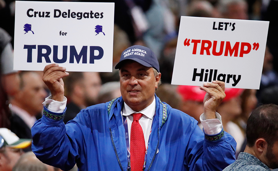 A delegate holds a sign calling for Ted Cruz delegates to support Donald Trump. (REUTERS/Jim Young)