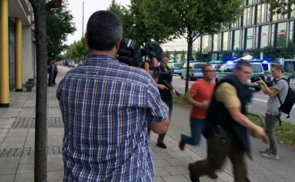 "rmed police responding to the shooting move past onlooking media. ""There is a major police operation under way in the shopping centre,"" Munich police said on Twitter, urging people to avoid the area. AP"