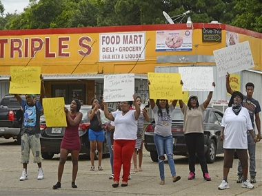 """Family and friends of Alton Sterling protest on the corner of Fairfields Ave. and North Foster Drive Tuesday afternoon, July 5, 2016, after was fatally shot in an altercation with Baton Rouge Police just after midnight, in the parking lot of the Triple S Food Store, in Baton Rouge, La. They chanted things including """"Hands up, don't shoot!"""" Officers responded to the store about 12:35 a.m. Tuesday after an anonymous caller indicated a man selling music CDs and wearing a red shirt threatened him with a gun, said Cpl. L'Jean McKneely. (Travis Spradling/The Advocate via AP)"""