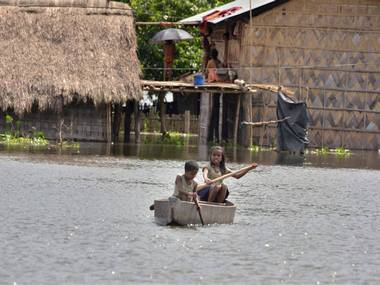 Children use a boat in a village near Kaziranga National Park. seven people have died so far in the floods affecting the state. PTI