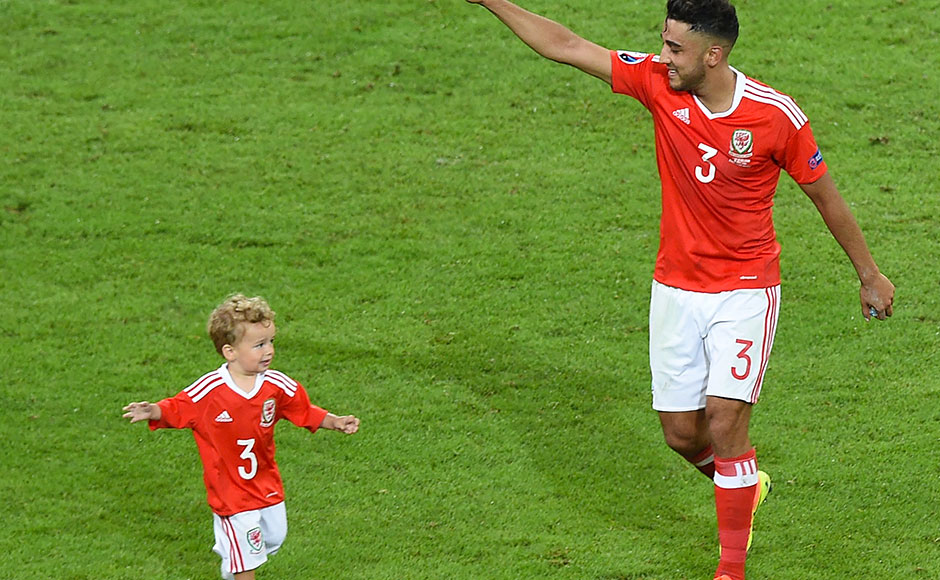 Wales' defender Neil Taylor celebrates with his son Marley at the end of the Euro 2016 quarter-final football match between Wales and Belgium at the Pierre-Mauroy stadium in Villeneuve-d'Ascq near Lille, on July 1, 2016. / AFP PHOTO / DENIS CHARLET