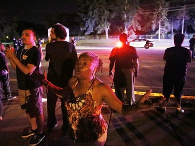 A woman joins others gathered at the scene of a police involved shooting on Wednesday, July 6, 2016 in Falcon Heights, Minn. St. Anthony Police interim police chief Jon Mangseth said the incident began when an officer pulled over a vehicle Wednesday in the St. Paul suburb. Mangseth said he did not have details about the reason for the traffic stop, but that at some point shots were fired. The man was struck but no one else was injured, he said. (Leila Navidi/Star Tribune via AP)