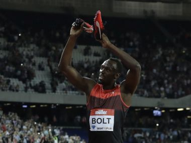 Usain Bolt of Jamaica applauds the crowd holding his shoes after he won the men's 200 meter race. AP