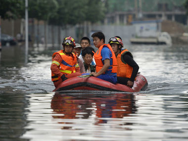 Rescuers use raft to ferry people. AP