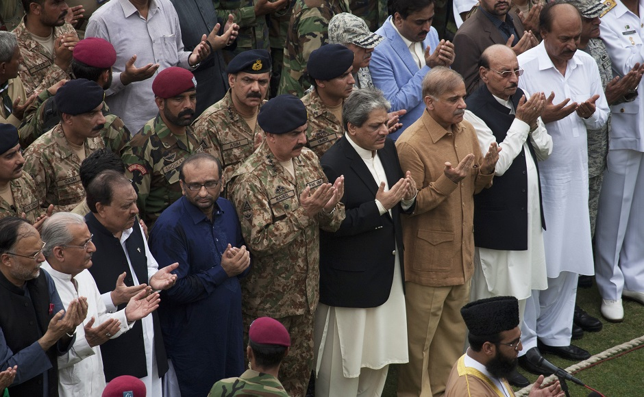 Pakistan's army chief Gen. Raheel Sharif, fifth from right in front row, attends the funeral of Pakistan's renowned social worker Abdul Sattar Edhi with others in Karachi, Pakistan, Saturday, July 9, 2016. Tens of thousands of people attended Saturday the state funeral for Pakistan's legendary philanthropist, Abdul Sattar Edhi, in Karachi, officials said. (AP Photo/Shakil Adil)