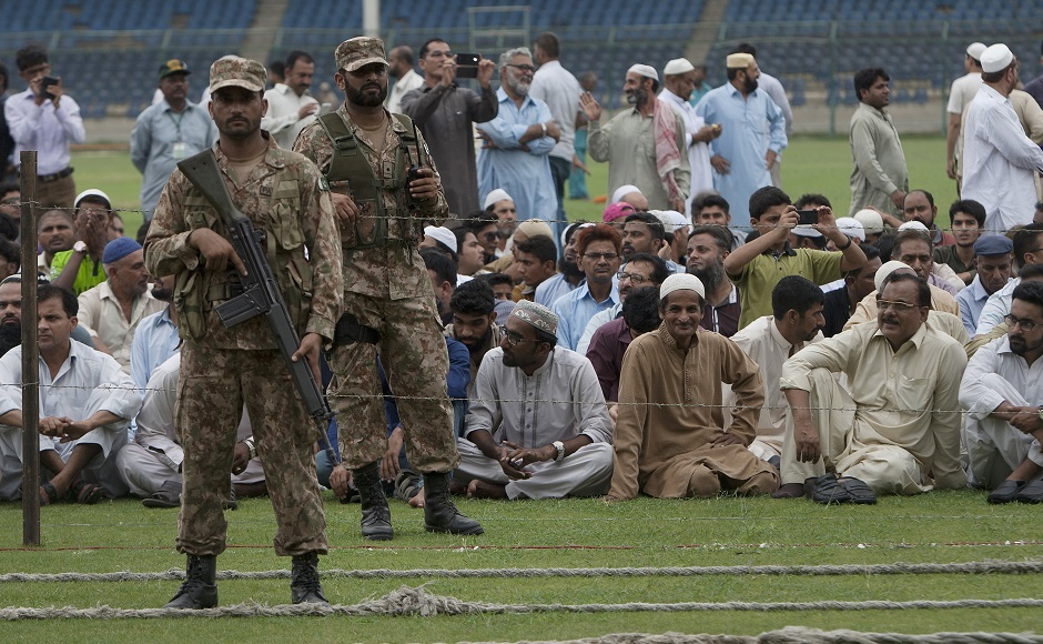 Pakistani soldiers stand guard as people wait for the funeral of Pakistan's renowned social worker Abdul Sattar Edhi in Karachi, Pakistan, Saturday, July 9, 2016. Pakistan's legendary philanthropist Abdul Sattar Edhi, who devoted his life to the poor and the destitute, died on Friday at a hospital in Karachi following a prolonged illness. He was 88. (AP Photo/Shakil Adil)